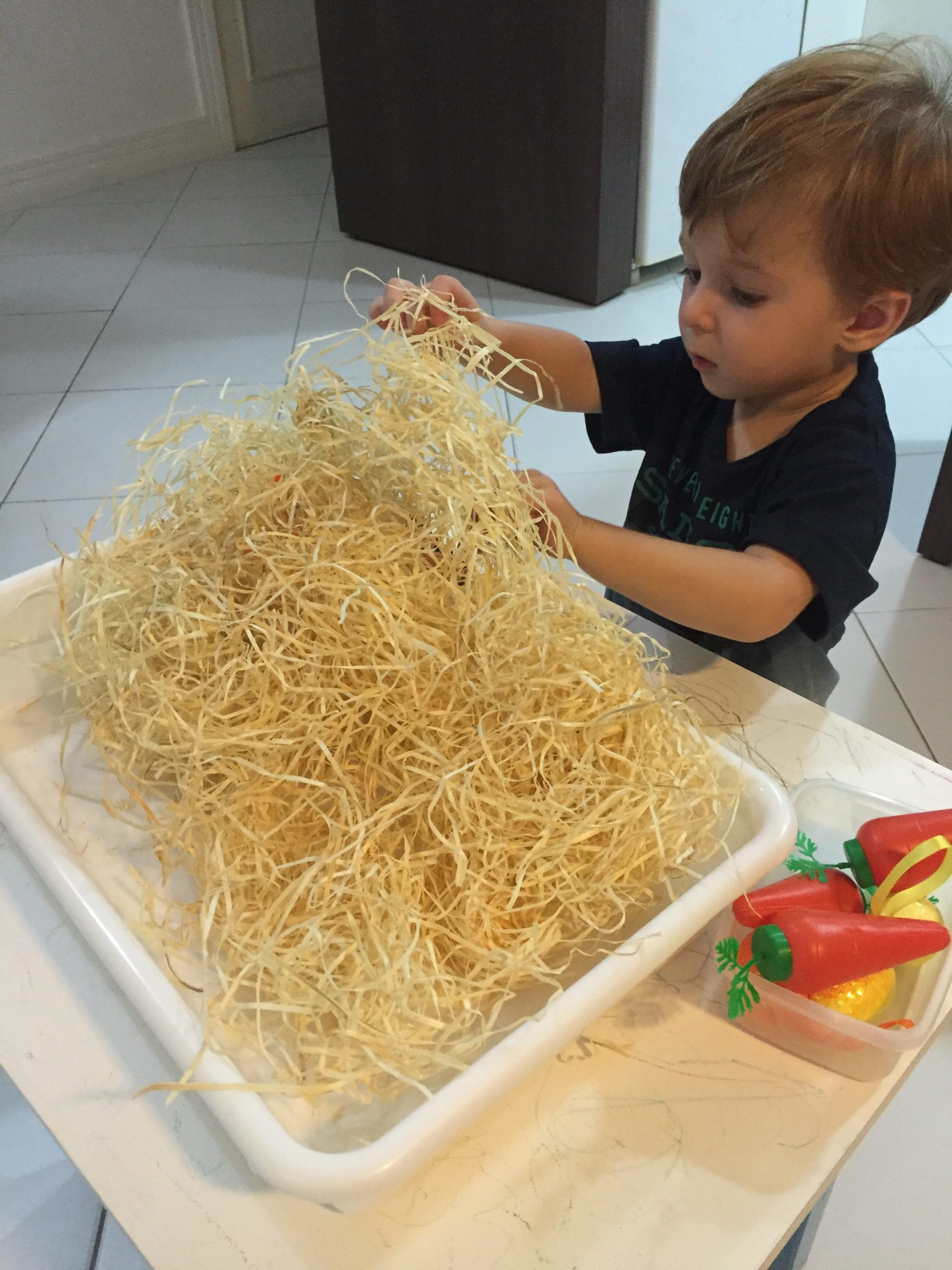 Augusto brincando com palha, bricadeira sensorial