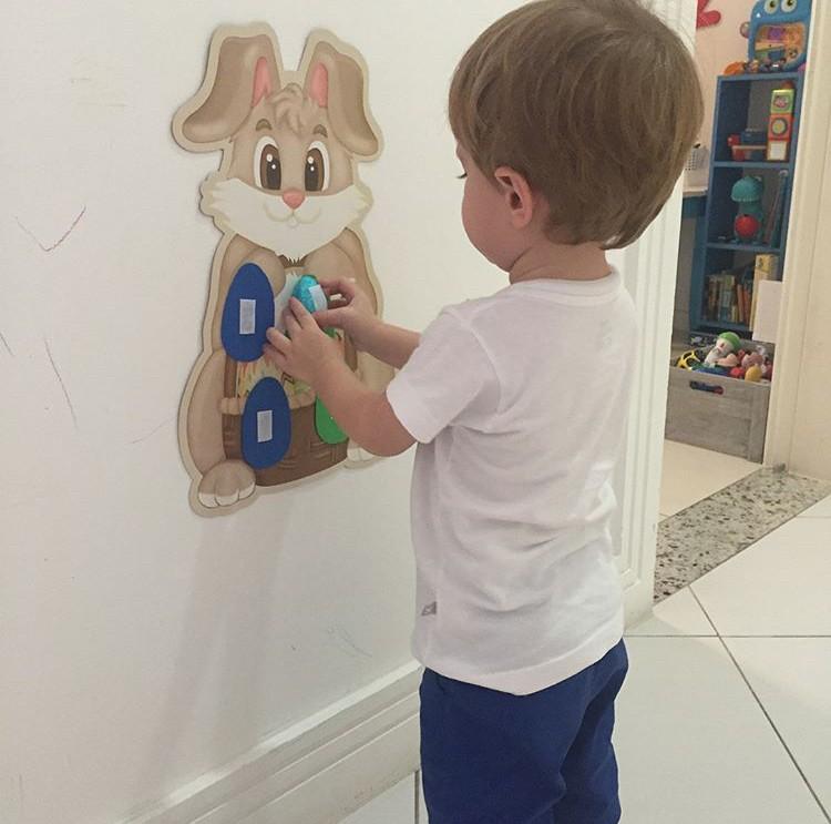 Augusto brincando com coelho de papel na parede